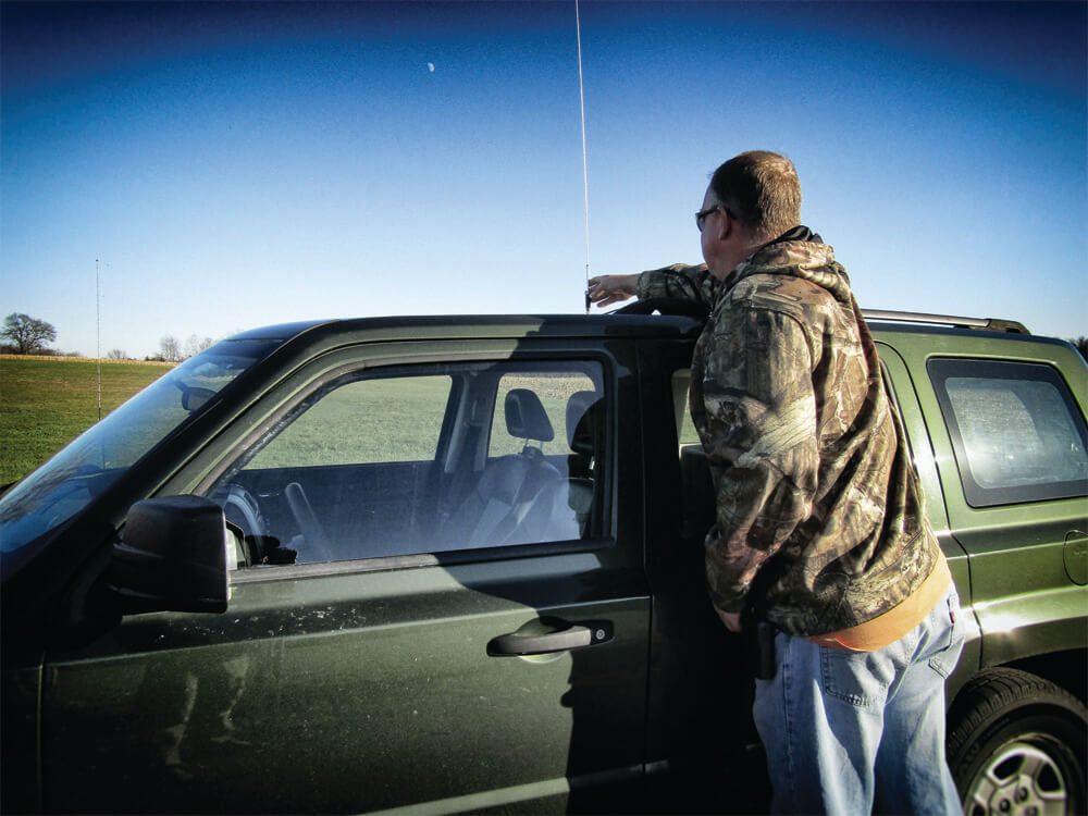 A man adjusting the radio antenna located on the top of his vehicle.