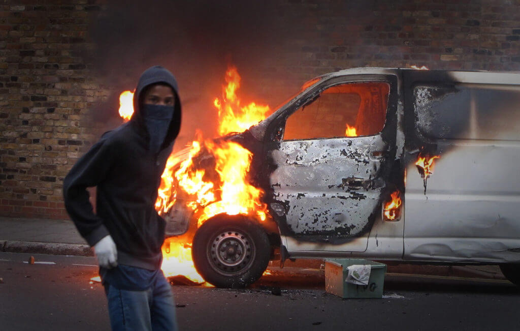 Vehicles parked in the rioters' paths are easy targets and are often smashed or torched as this van was during riots and looting near London in 2011.
