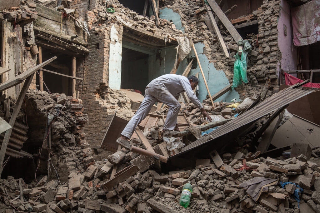 A man searching for survivors in a building destroyed by an Earthquake in Nepal