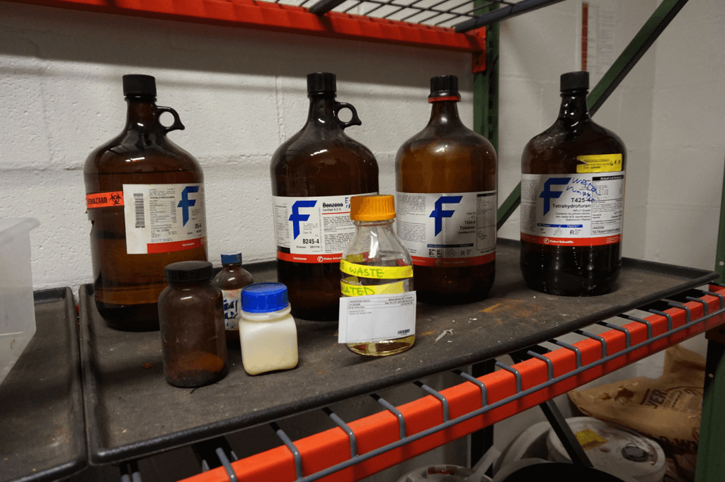 Bottles of discarded chemicals in a cell, categorized for disposal.