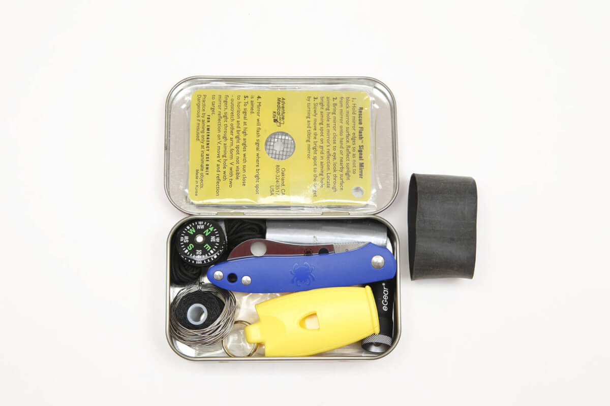 The Roadie, a small pocket knife, inside of a altoids tin pocket survival kit