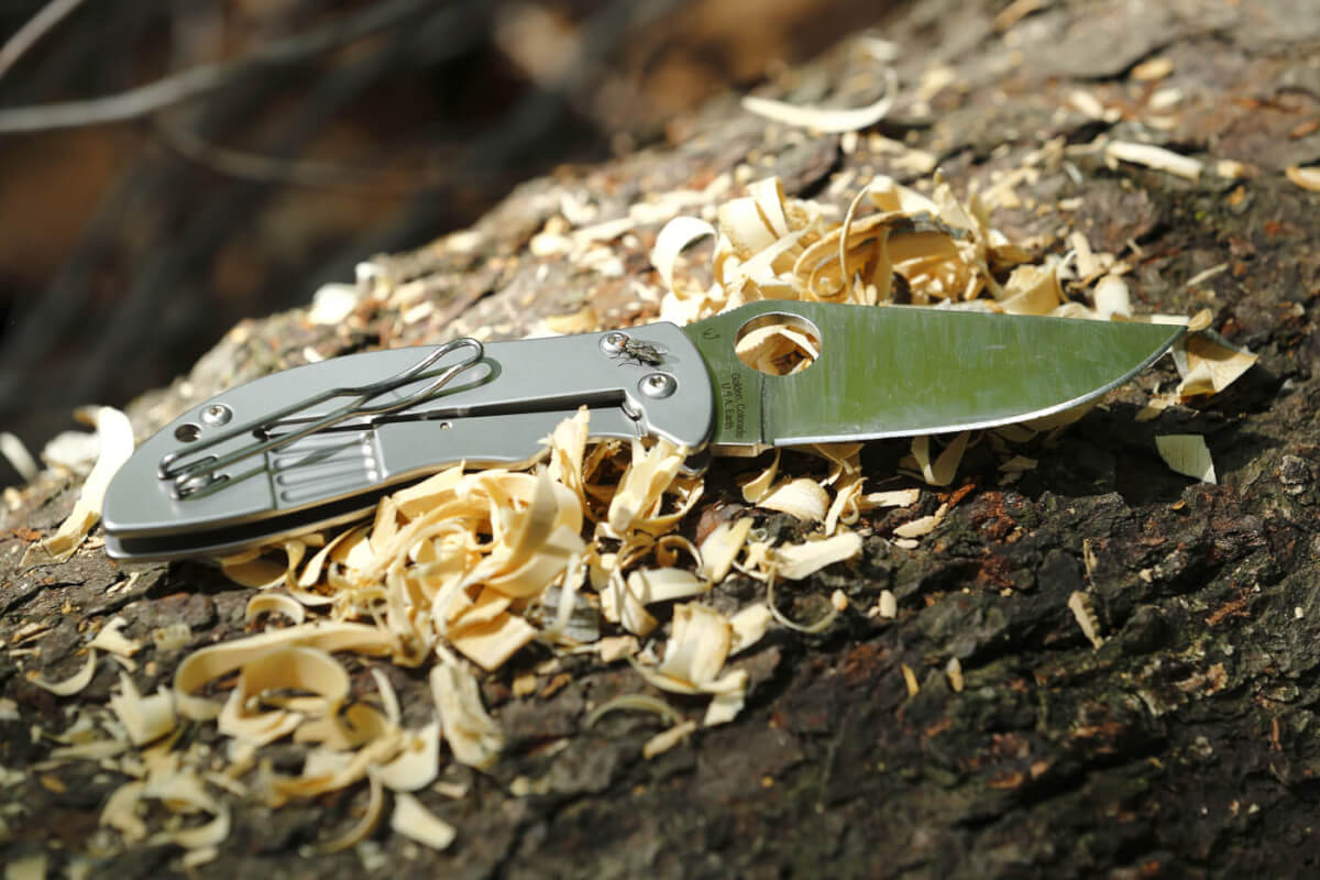 The Foundry folding knife, sitting atop tinder that was made from it's use