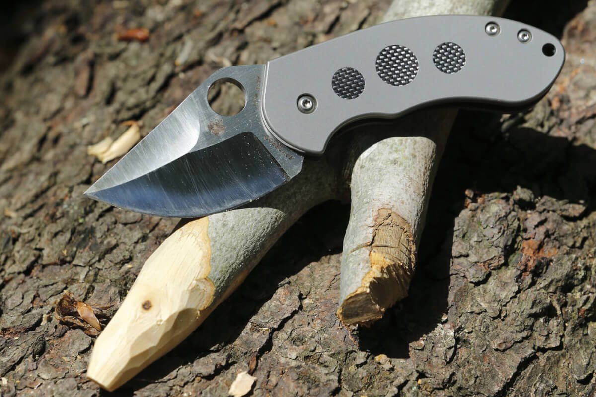 The Burch Chubby folding knife, on top of a wooden stake it's blade was used to carve