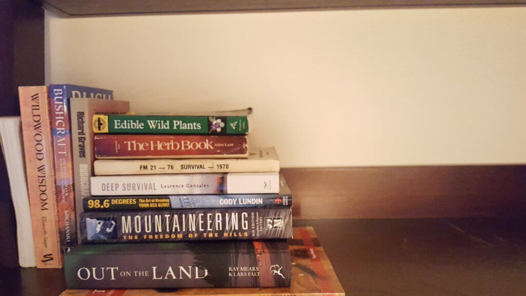 Various survival books on a bookshelf