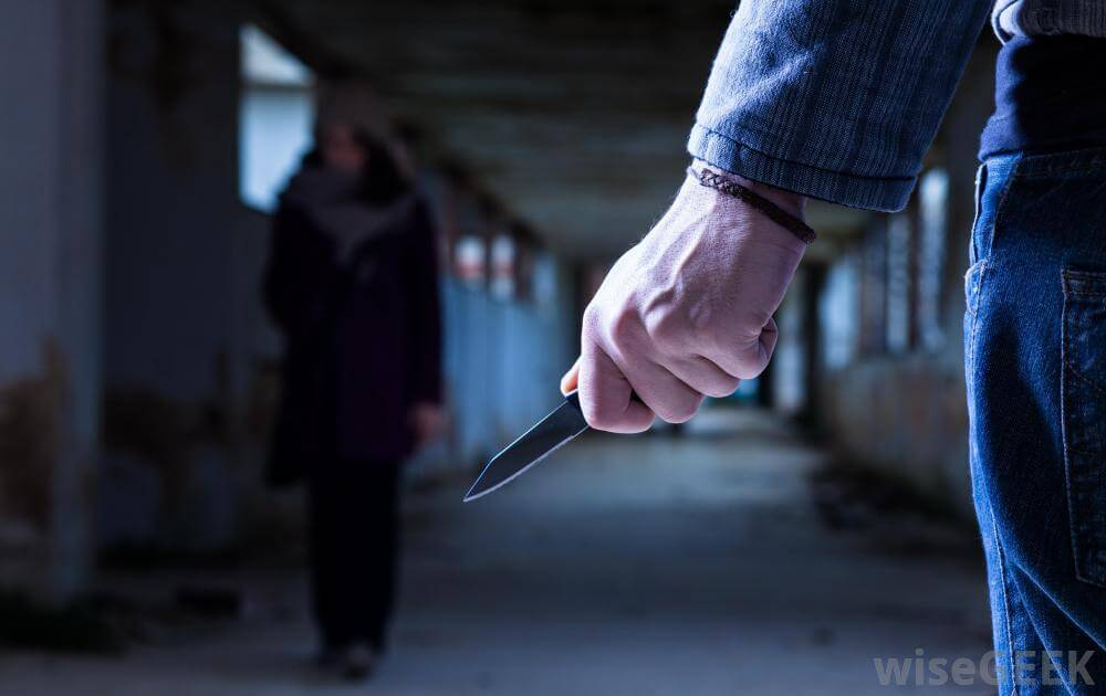 A mugger approaching a lone person with a knife