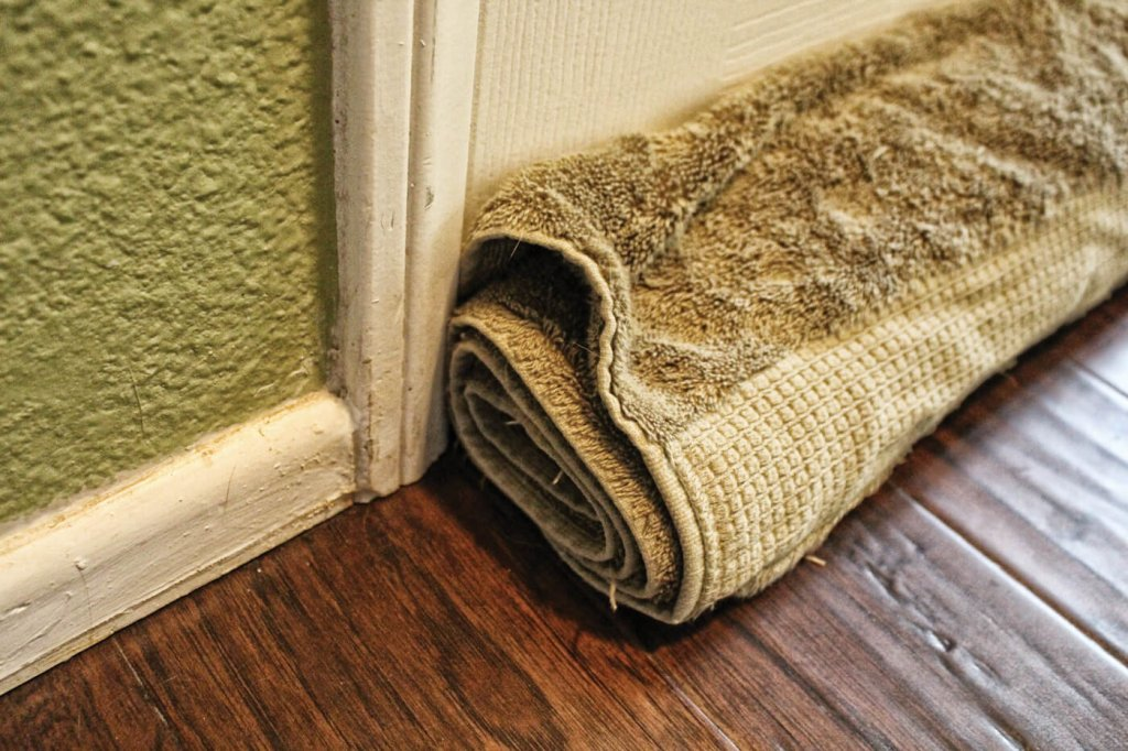 Thick towel against a wall covering gap between door and floor.