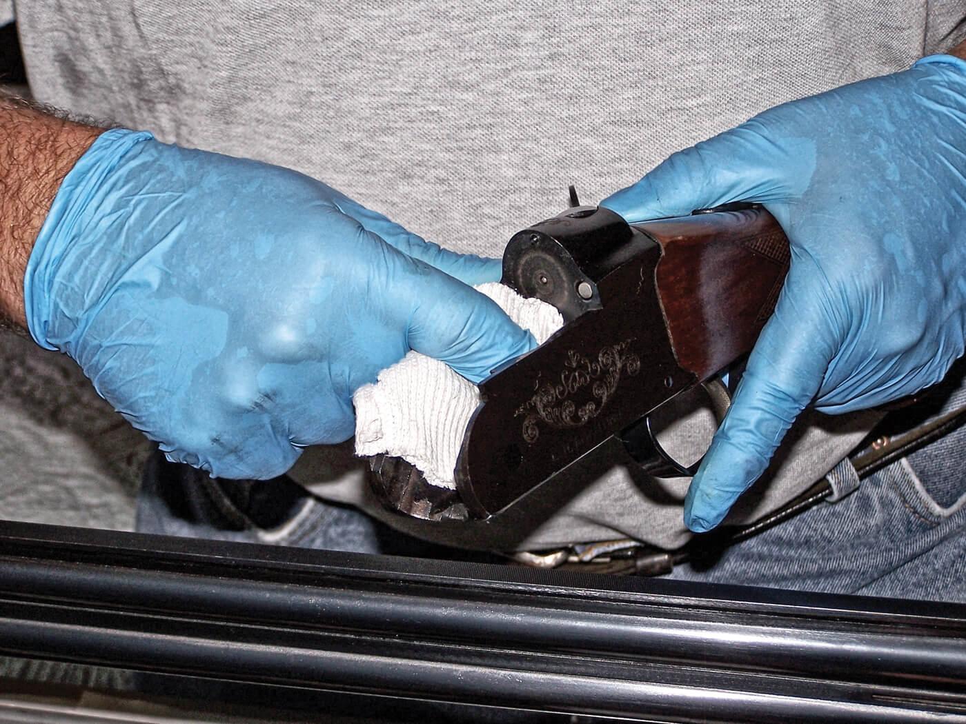 Gloved hands cleaning an over-under shotgun