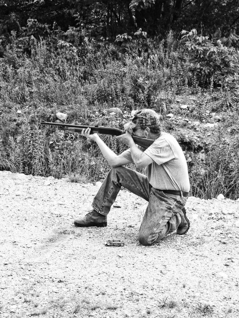 Man firing shotgun while kneeling
