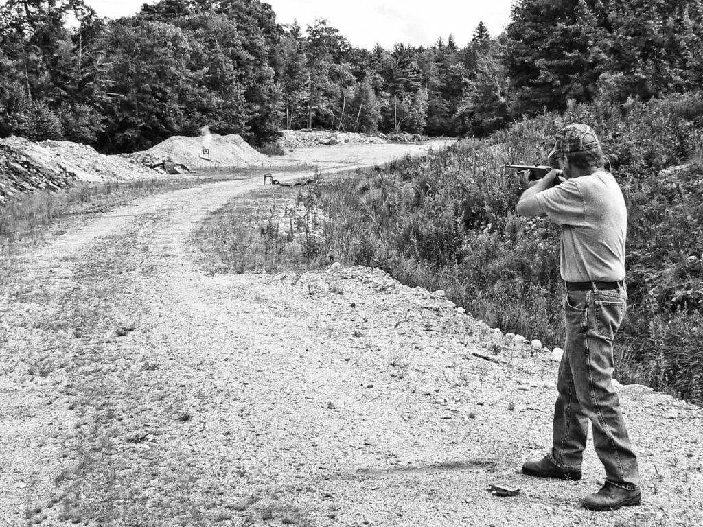Man firing shotgun while standing