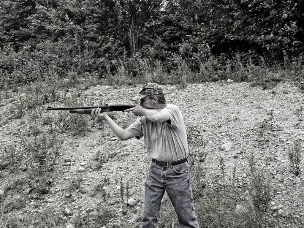 Man aiming shotgun while standing