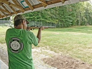 Man aiming and firing Marlin rifle down range