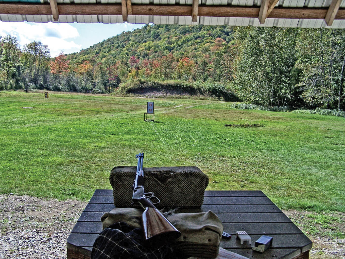 Lever-action rifle on a table set up in front of a 25-yard target in outdoor range