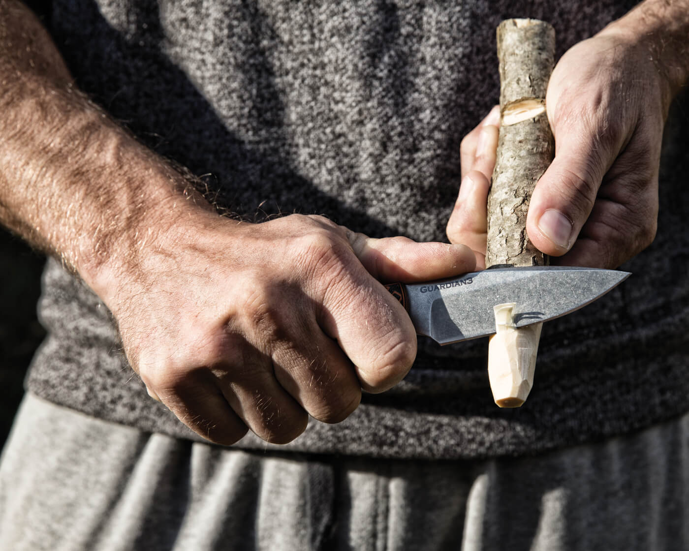 Man using Guardian3 knife to carve wood