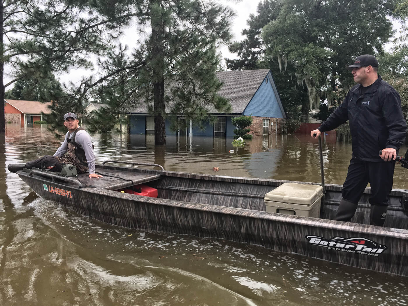 Gator-Tail boat ferrying two men through flooded streets after Hurricane