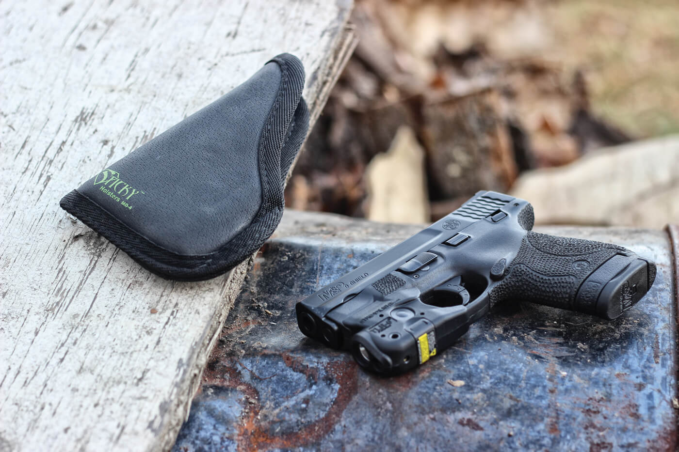 Smith & Wesson Shield pistol with Streamlight attached, shown next to Sticky holster
