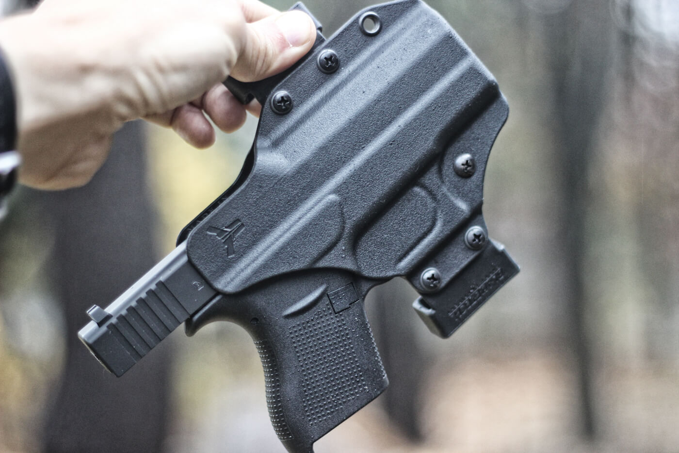 Man holding up Glock 43 in Blade-Tech Eclipse OWB holster, without magazine and slide retracted
