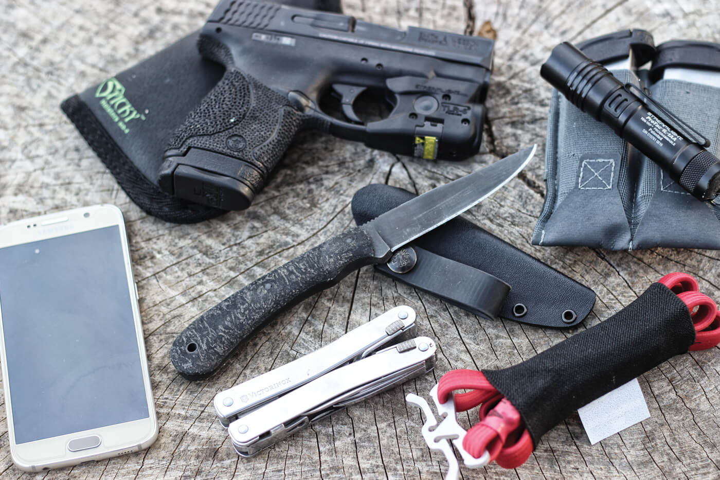 EDC items that include a Smith & Wesson Shield pistol in a Sticky holster, flashlight, spare magazines, cellphone, fixed-blade knife, multi-tool and tourniquets