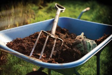 Pitchfork on wheelbarrow with soil and compost