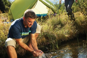Man washing hands with stream water to maintain proper hygiene