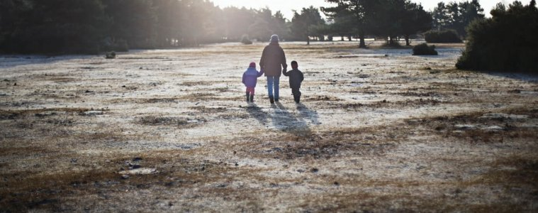 Man walking into the sunset with two children