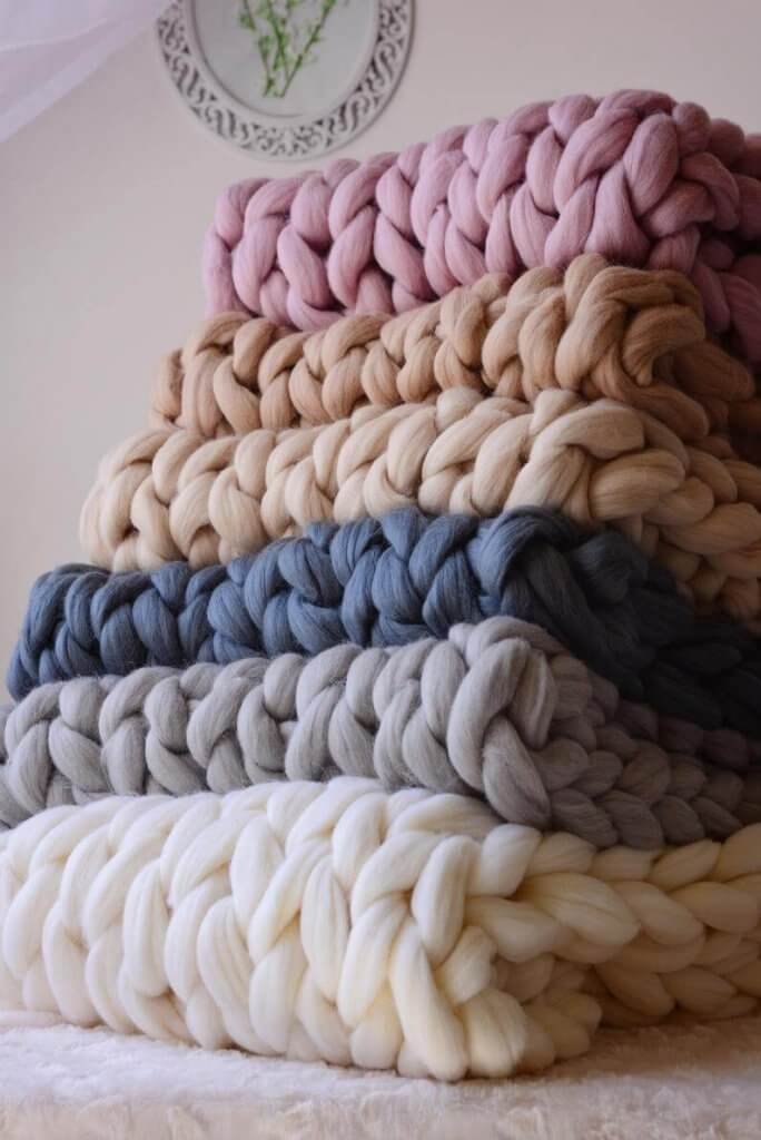 Stack of knit blankets in a variety of colors
