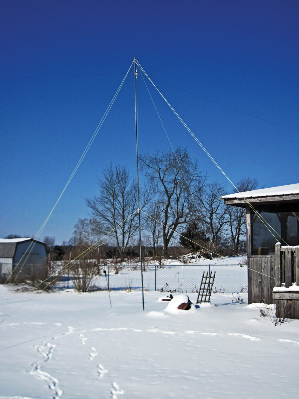 Tight guy lines keep the author's HF antenna standing against strong winds.