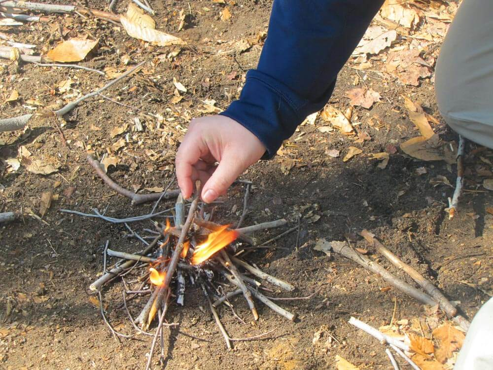 Put down a good-sized pile of tinder, then once it is lit start to place the kindling over it.