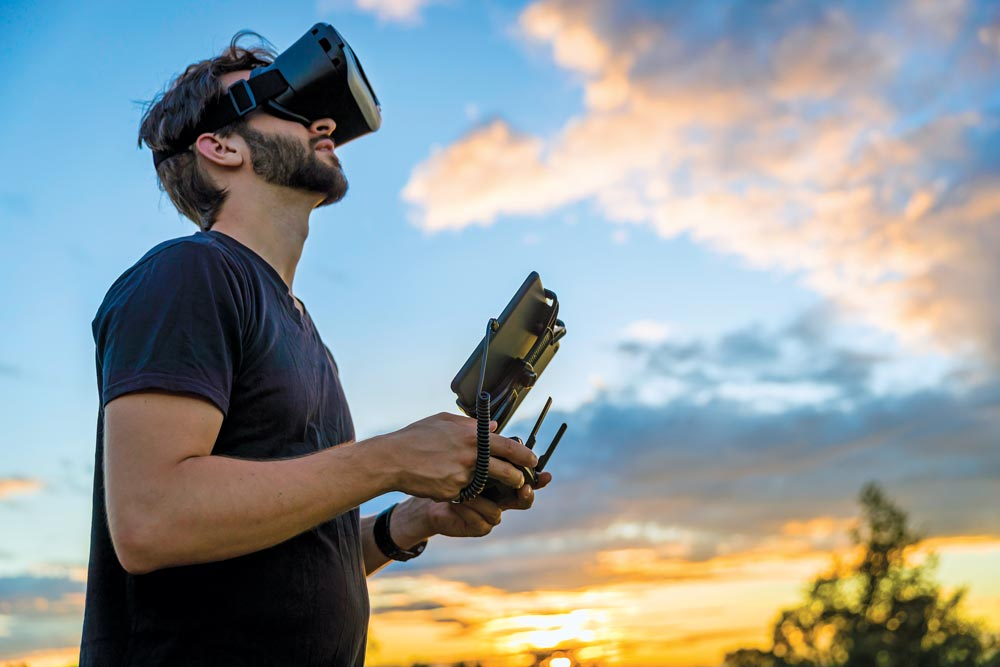 A man flies a drone with a virtual reality headset.