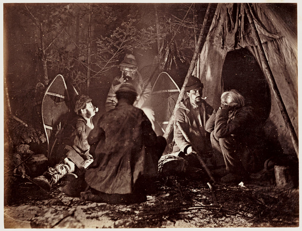 Trappers gather at the campfire after a long day of tracking in 1860s Canada.