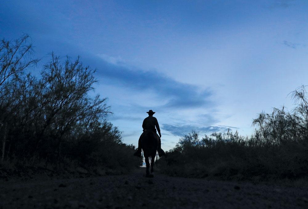 A U.S. Border Patrol agent on horseback tracks human and drug smugglers.