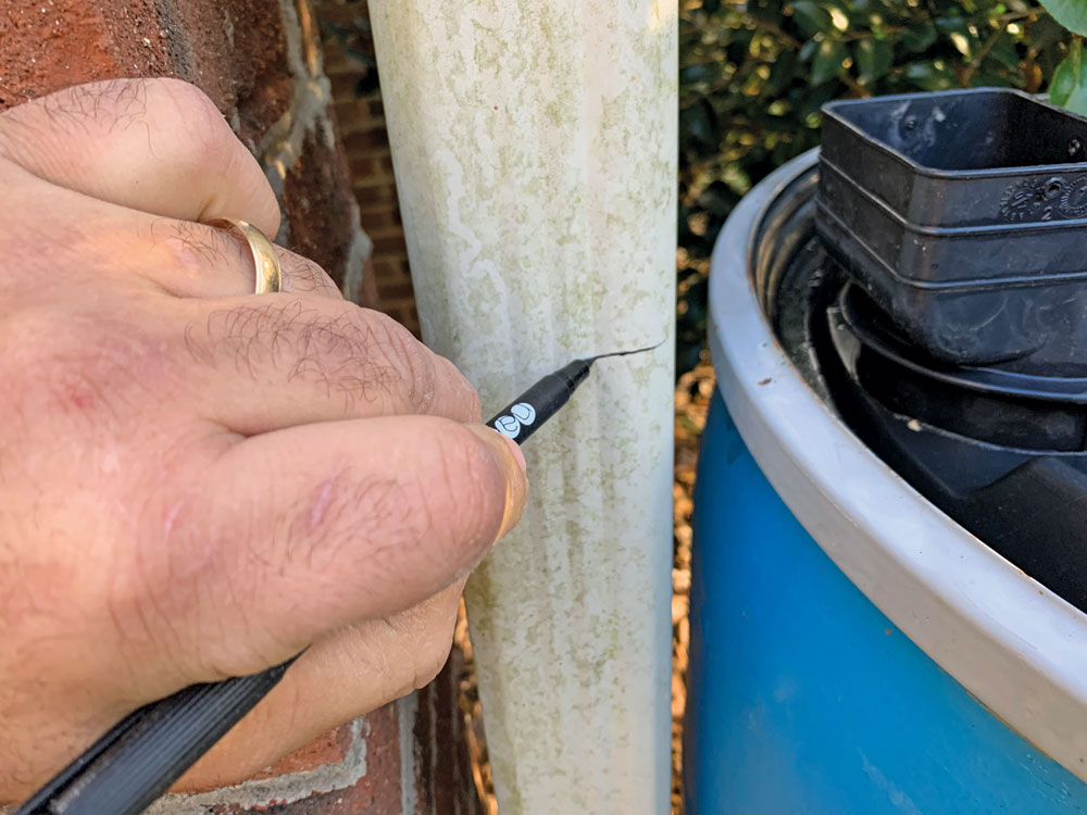 Marking the location to cut the downspout.