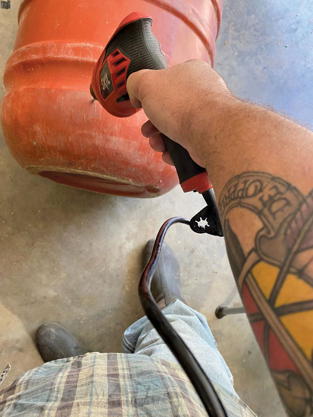 Drill a hole near the base of the rain barrel.