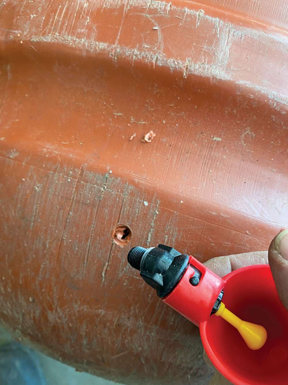Carefully screw the watering cup assembly into the drilled hole.
