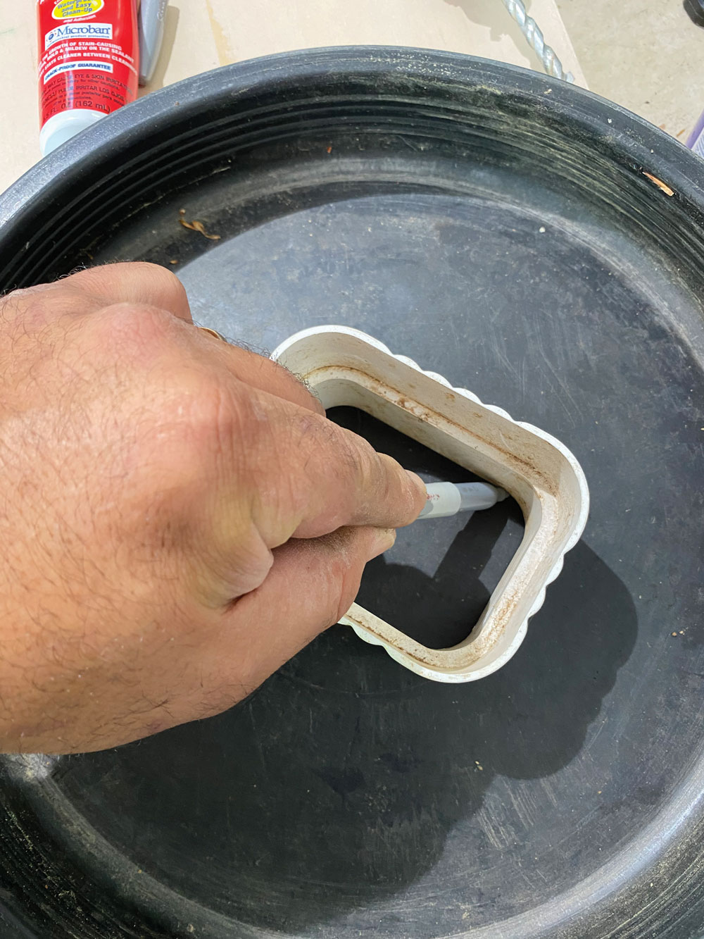 Use a marker to draw an outline of the downspout or downspout adapter where you want it to enter the barrel's lid