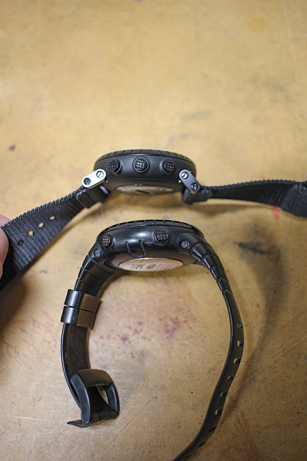 The newer hinged watch straps (top) allow you to lay the watch on a flat surface, such as a map, unlike the straps on the earlier Suunto Core model (bottom).