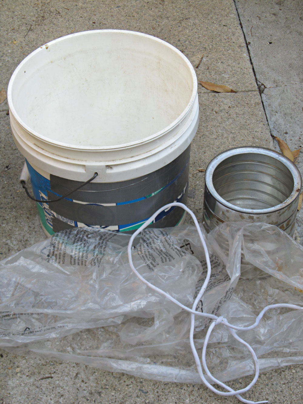 A still can be made in the backyard with these parts: a can, bucket, sheet of plastic and some cord.