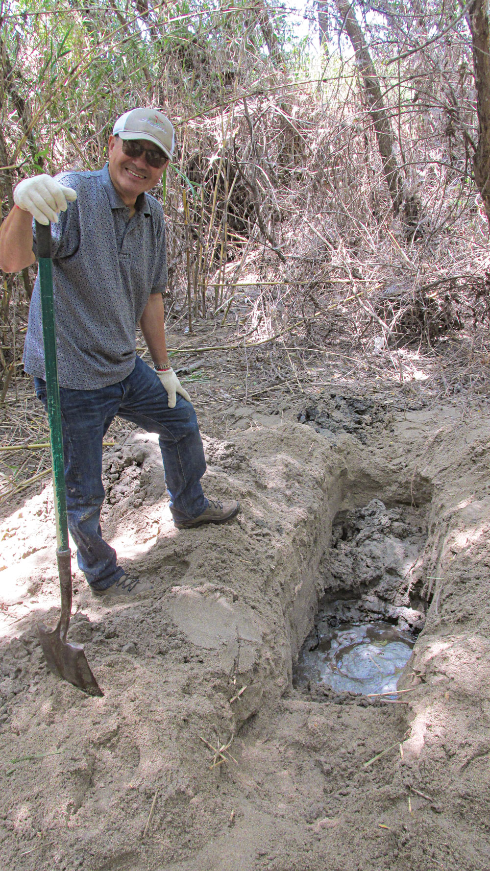 """This man was digging a """"body hollow"""" (a type of primitive shelter) when he hit water! He then built a different shelter nearby, and his """"well"""" provided water."""
