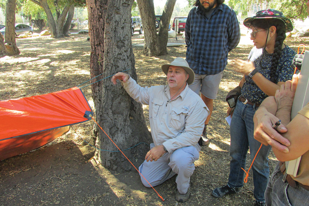 Instructor Keith Farrar shows how to turn a grommeted tarp into a quick shelter.