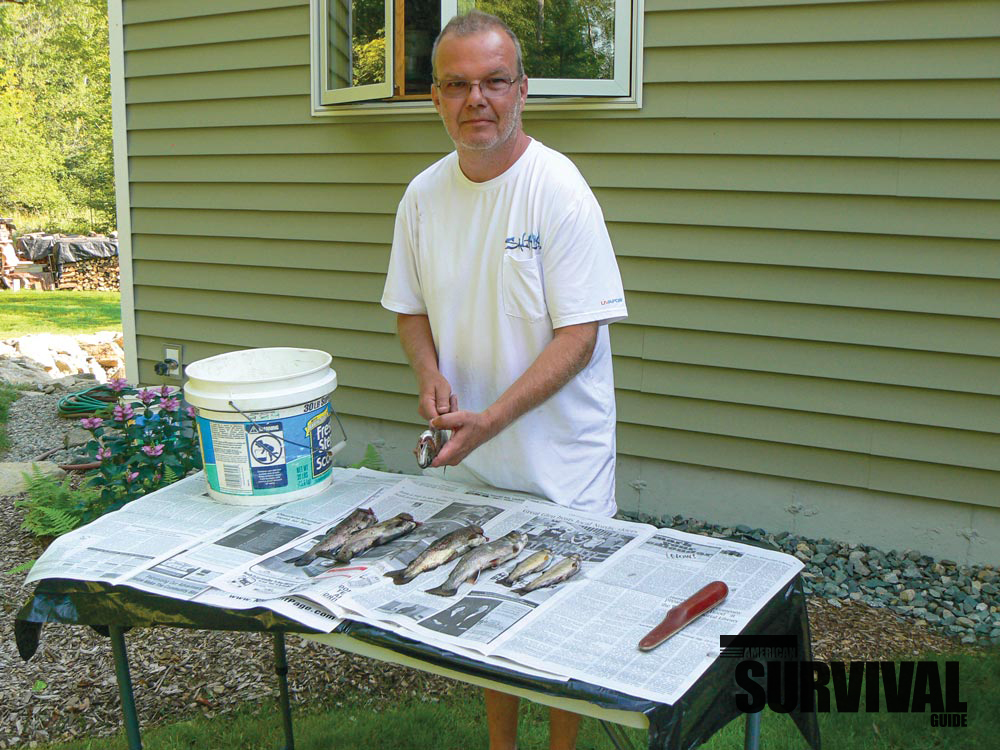 Self-sufficiency means securing food whenever you can. In this case, the author is preparing some trout for the grill.